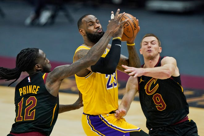 Los Angeles Lakers' LeBron James (23) drives to the basket between Cavaliers defenders Taurean Prince (12) and Dylan Windler (9) in the second half of an NBA basketball game, Monday, Jan. 25, 2021, in Cleveland. The Lakers won 115-108. (AP Photo/Tony Dejak)