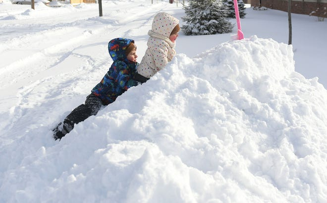 After a 10-inch snowfall the night before, West Prescott, 5, helps his sister Ellie, 2, to climb a snow pile on 10th Street on Jan. 26, 2021, in Ames.