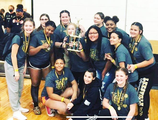 Members of the Leesville Lady Cat powerlifting team pose with the first-place trophy after winning the team title Saturday at the Wampus Cat Invitational.