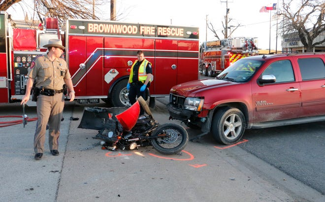 A Texas Department of Safety trooper and a Brownwood police officer walked near a wrecked motorcycle after the cycle was involved in a collision with a Chevrolet Suburban, also pictured.