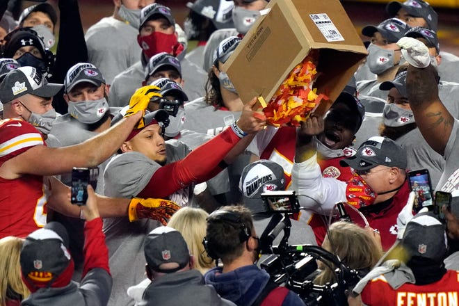 Kansas City Chiefs players dump a box of confetti on head coach Andy Reid after the AFC championship game against the Buffalo Bills on Sunday in Kansas City.