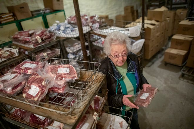 Linda Oiler pulls a package of brats from a walk-in freezer.