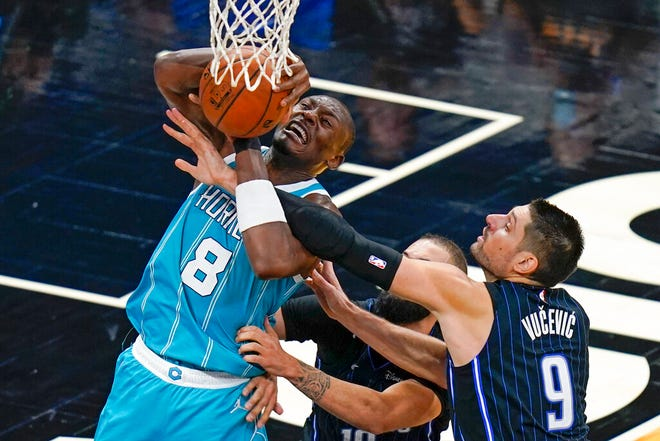 Charlotte Hornets center Bismack Biyombo (8) is fouled by Orlando Magic center Nikola Vucevic (9) as he goes up for a shot during the second half of an NBA basketball game, Monday, Jan. 25, 2021, in Orlando, Fla. (AP Photo/John Raoux)
