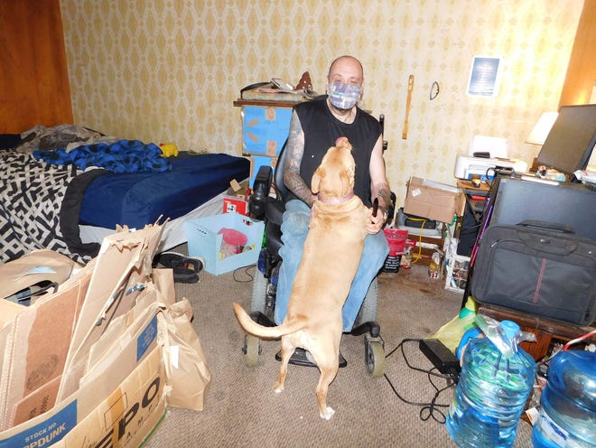 Lee Holtz Jr. and his dog, Deogee, are shown inside their room at the Glen Ridge Motel in East Herkimer. Holtz is the only tenant left in the motel complex that has been condemned due to codes violations. He is planning to move out as soon as he can secure an apartment and help to get there with his belongings.