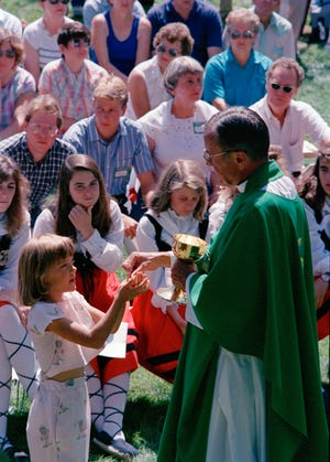 In this 1988 file photo Rev. Joseph Hart dispenses communion during an outdoor Mass celebrated for participants of the Basque Festival in Buffalo, Wyo. On Tuesday, the Vatican's Congregation for the Doctrine of the Faith cleared Hart of seven accusations of abuse, determined that five others couldn't be proven 'with moral certitude' and that two cases involving boys, who were 16 and 17, couldn't be prosecuted given the Catholic Church didn't consider them minors at the time of the alleged abuse, the diocese said. (AP Photo/Dean Wariner, File)