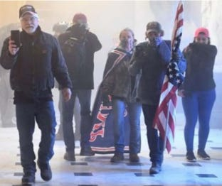 An FBI court filing says Middleburg residents Rachael Pert and Dana Winn acknowledged being the caped woman and flag-carrying man in this Jan. 6 photo  taken inside the U.S. Capitol.