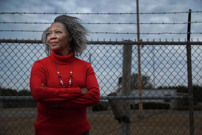 Jannie Everette, whose mother survived the Feb. 3, 1971 fire and explosion of the Woodbine Thiokol plant, stands in front of the fenced-off former factory site. Everette has made it her mission to remember the day 29 workers died and dozens more were injured. A 50th anniversary event will be held Feb. 3 at the Camden County High School football stadium.