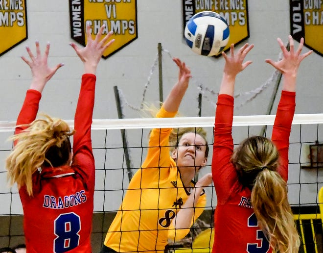 Garden City Community College's Reagan Karlin, center, drives the ball through a pair of Hutchinson defenders for a kill Monday during a volleyball match at Perryman Athletic Complex. The Broncbusters won the home opener, the first time GCCC had beaten the Blue Dragons in nearly 20 years.