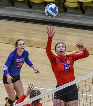 Hutchinson's Kristina Head, right, tips the ball over the net as teammate Shelby Reeder looks on Monday during a volleyball match in Garden City.