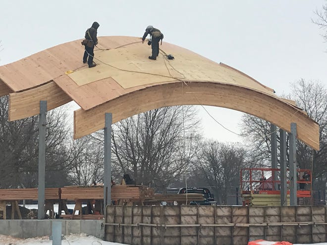 Two workers from Mesic Vale in Galesburg were hurrying Monday afternoon to put the sheeting on the roof on the new stage in Galva's Wiley Park. They were still working Monday afternoon when the snow began to fall. City administrator David Dyer said Monday that he was not sure what kind of a roof, metal or shingle that Jane Doss would choose for the project since she had donated the funds for the project in  memory of her parents Kyle and Joan Doss.