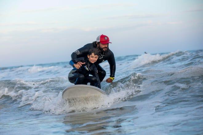 Chris Antão, director executivo Gnome Surf, a surfar com um aluno, na South Shore Beach, em Little Compton, R.I.