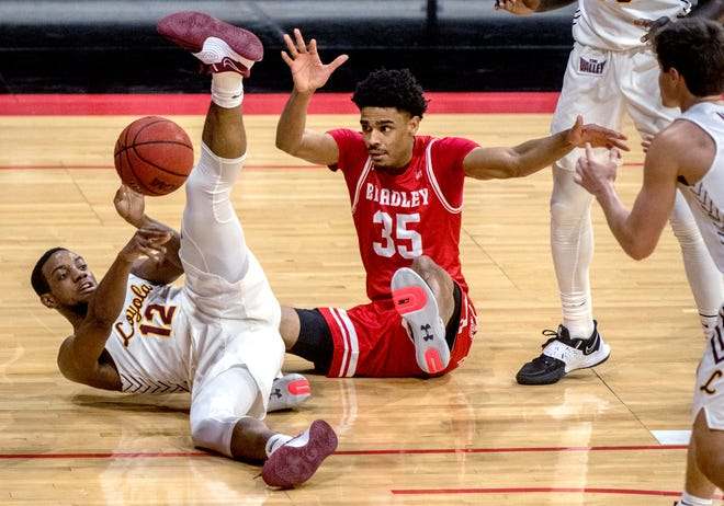 Loyola's Marquise Kennedy (12) tries to pass the ball past Bradley's Darius Hannah (35) while falling to the court in the second half Monday, Jan. 25, 2021 at Carver Arena in Peoria.