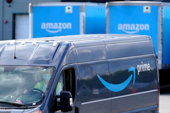 An Amazon Prime logo appears on the side of a delivery van as it departs an Amazon Warehouse in Dedham. Online shopping has been a lifeline for many as the virus pandemic shuttered stores and kept people at home.