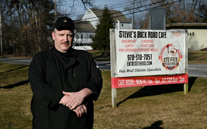 Stevie Dembro, owner of Stevie's Backroad Cafe in Hudson, stands next to the sign for his cafe on Main Street, Jan. 26, 2021. Dembro has created a Feed a Neighbor program where he provides meals for people in need. He is also planning a series of comedy show fundraisers this weekend for the program.