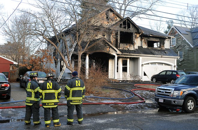 Natick firefighters survey the scene Tuesday morning, after a man died in an overnight house fire at 29 Longfellow Road in Natick , Jan. 26, 2021.