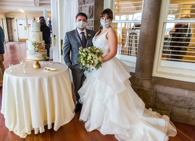 Paige Zuber and Michael Weishaus, the mock bride and groom, both of North Providence, pose with the mock cake.