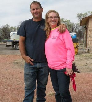 In this 2017 file photo from the La Junta Tribune Democrat, Justin and Wendy Schneider pose for a photo outside their paving business in Colorado.