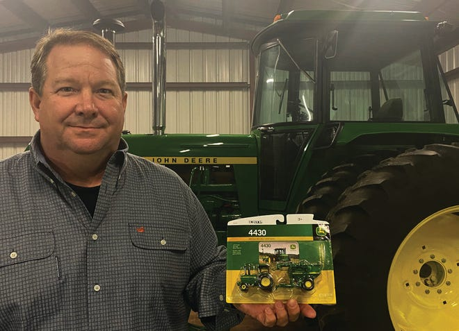 Rob Marrionneaux displays the tiny version of his newly acquired 1977 John Deere 4430 tractor, which looms in the background at his home in Grosse Tete. Marionneaux purchased the mint-condition vintage tractor through an auction.