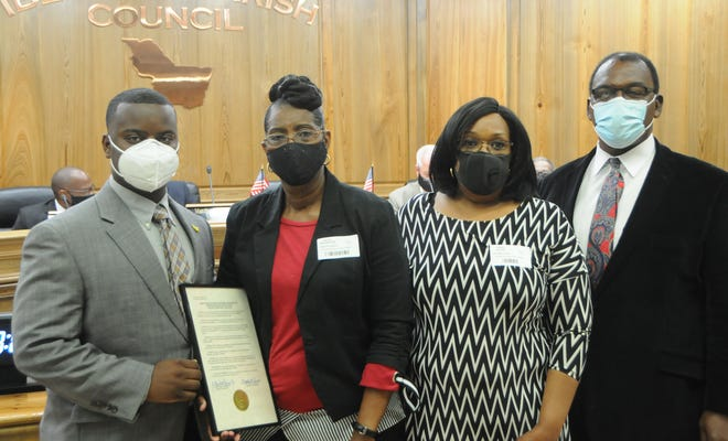 """Iberville Parish Council Raheem Pierce of District 6 presents a plaque of condolence to the family of Gerald Lee """"Lightning"""" Williams."""