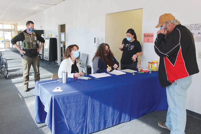 Tom Barker (right)checks in during a COVID-19 Point of Distribution (POD)vaccination day Thursday at Pratt Community Center, with Amy Schrag (at the table from the left), Crysta Mayer and Darcie Van Der Vyver. Pratt County Sheriff Jimmy White kept a watch on the event.
