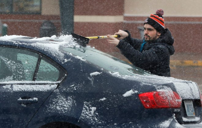 Jack O'Marra cleans the snow from his car as he leaves work Tuesday afternoon in Warwick.
