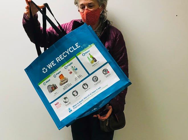 Lane County Waste reduction Specialist Sarah Grimm holds one of the tote bags being distributed to 2,000 households as part of a pilot program to study recycling habits and how to change them.