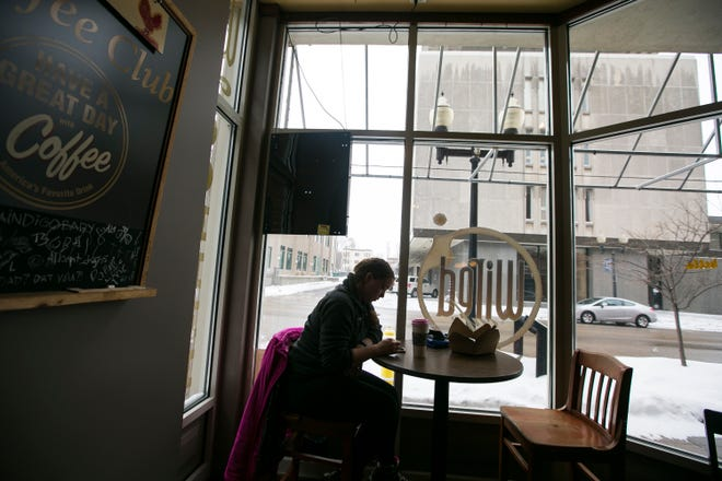 Rockford resident Shane Baker sips coffee and surfs the internet on her mobile phone while sitting inside Wired Cafe on Tuesday, Jan. 26, 2021, in Rockford. Baker is a regular at the coffee shop who is happy that coronavirus restrictions have loosened.