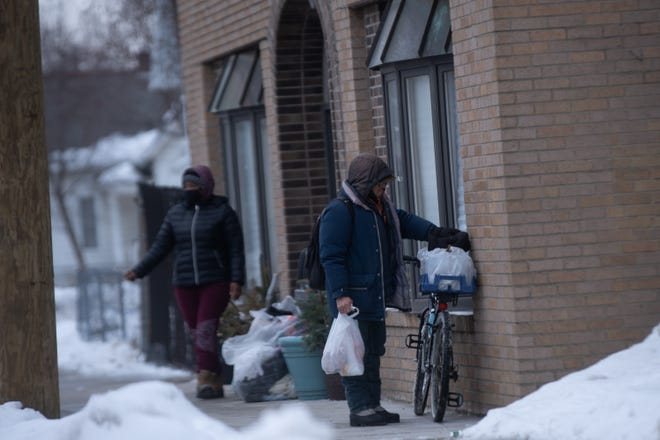 Two people wait outside of Miss Carly's, a nonprofit that serves people in need, on Monday, January 25, 2021 in Rockford.