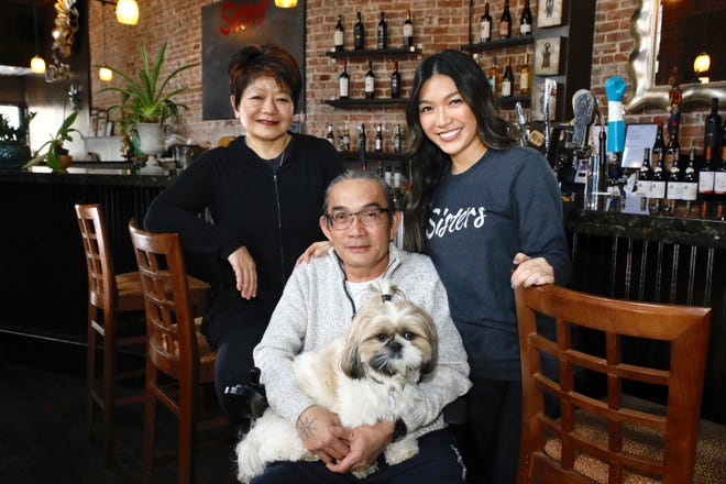 Chintana Sengchannavong, left, her husband Viboun Sengchannavong, holding Tofu, his 1-year-old Shih Tzu service dog, and daughter Megan Sengchannavong are shown here Tuesday, Jan. 26, 2021, at Sisters Thai Cafe in Rockford. The family-owned downtown restaurant recently received funding from Barstool Sports to help them weather the coronavirus pandemic.