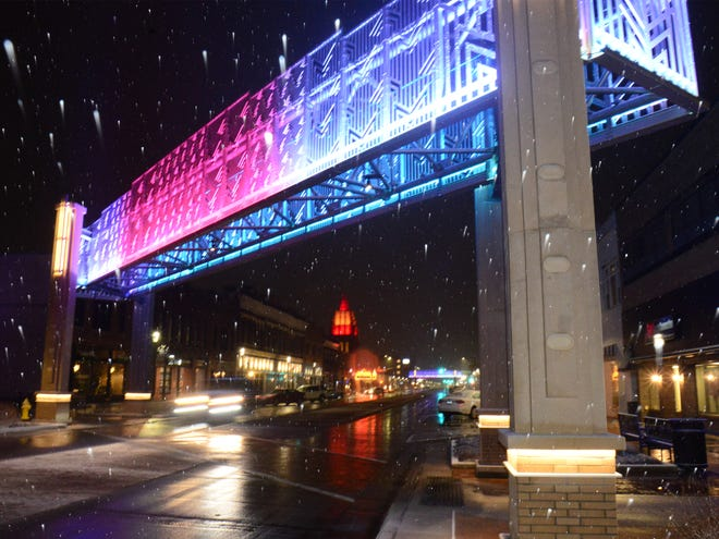 Snowflakes fall as a vehicle drives under the overhead crosswalk structure in downtown Salina on Monday evening.