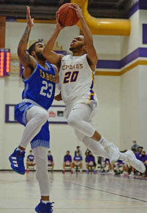 Kansas Wesleyan's Nate Leach (20) leaps toward the basket as Tabor's Andre Nelson (23) defends during Monday's game at Mabee Arena.