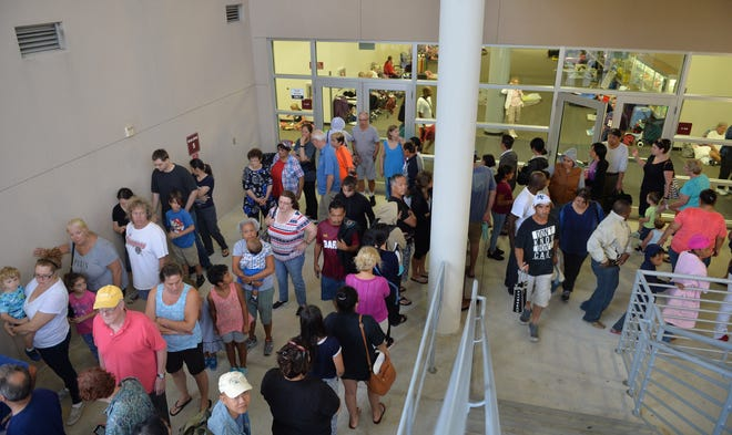 People stand in line for breakfast being served in the disaster shelter at Riverview High School in Sarasota in advance of Hurricane Irma in 2017. The shelter quickly reached capacity and closed to new evacuees. Sarasota County is in the process of hardening schools in mid-county into storm shelters.