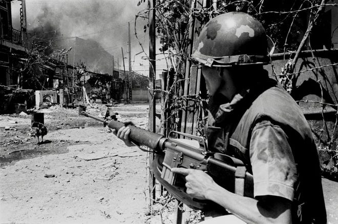 In this early 1968 file photo, a South Vietnamese soldier takes a position on a Saigon street during the Tet Offensive. Early on the morning of Jan. 31, 1968, as Vietnamese celebrated the Lunar New Year, or Tet as it is known locally, Communist forces launched a wave of coordinated surprise attacks across South Vietnam. The campaign, one of the largest of the Vietnam War, led to intense fighting and heavy casualties in cities and towns across the South.