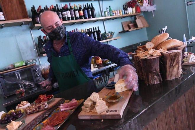 David Rishel puts together some charcuterie boards at The Cheese Board in the Old Wilmington City Market along Water Street in downtown Wilmington, N.C. Friday Jan. 8, 2021.