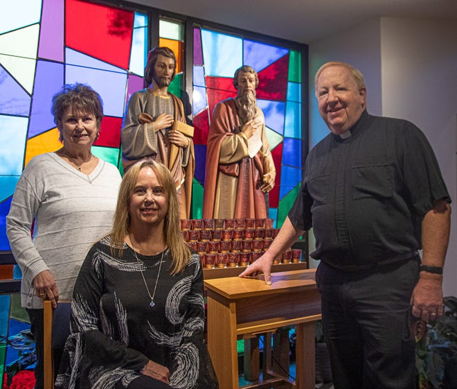 Kathy Bascom , DeLisa Conway and Father Thomas Tully stand before statues of Saints Joseph and Paul. Bascom is project coordinator for the church's 200th anniversary which will be recognized in programs through much of the year. [Bill Hand / Sun Journal Staff]