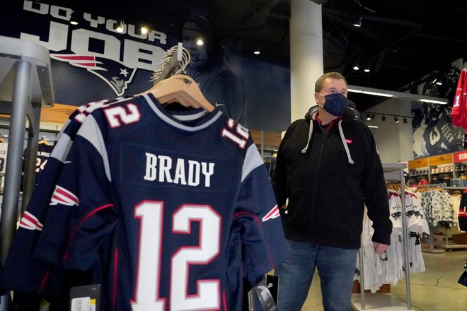 Football fan Brian Pope browses for Tom Brady jerseys in the pro shop at Gillette Stadium on Monday.