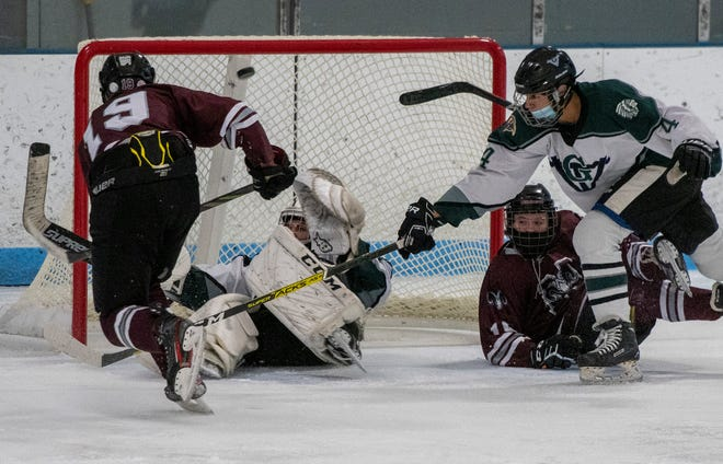 Northbridge's Ryan Couture scores over Grafton goalie Reed Henson with Northbridge's Logan Krupski and Grafton's Ryanne Chibani in the play, left to right, at the Buffone Skating Arena Monday, January 25, 2021.