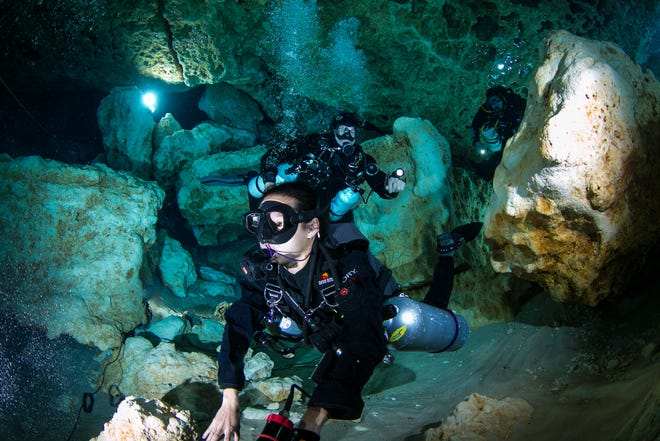 Divers Amy Vu, front, Rob Culbert and Guy Bryant make their way through the cavern in the Ball Room at Ginnie Springs in High Springs, Florida in this April 2017 file photograph.  [Alan Youngblood/Ocala Star-Banner]