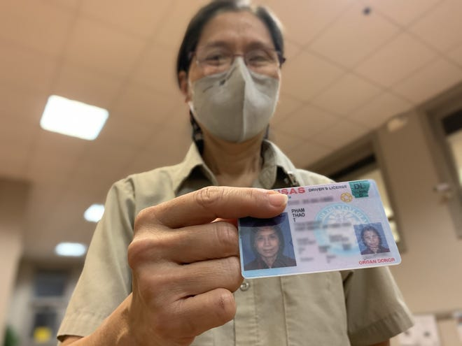 Fort Smith Public Schools Custodian Thao Pham shows her Arkansas driver's license on Thursday, Jan. 21, 2021, at the Fort Smith Adult Education Center. Pham said she studied for four months to get her driver's license when she arrived in Fort Smith in 2009.  Pham's personal information on the license has been intentionally blurred out on the photo.