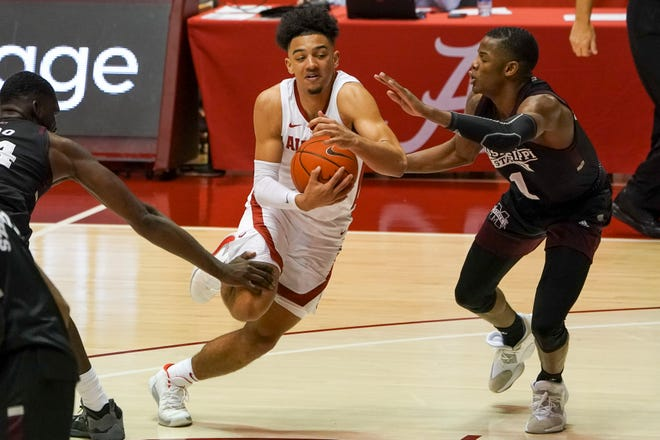 Jan 23, 2021; Tuscaloosa, Alabama, USA; Alabama Crimson Tide guard Jaden Shackelford (5) drives to the basket against Mississippi State Bulldogs guard Iverson Molinar (1) during the second half at Coleman Coliseum. Mandatory Credit: Marvin Gentry-USA TODAY Sports