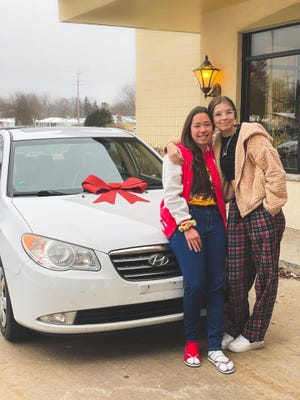 Hailey Bridges, right, and Hokule'a Taniguchi, left, sit on the 2008 Hyundai won at the Holiday party raffle
