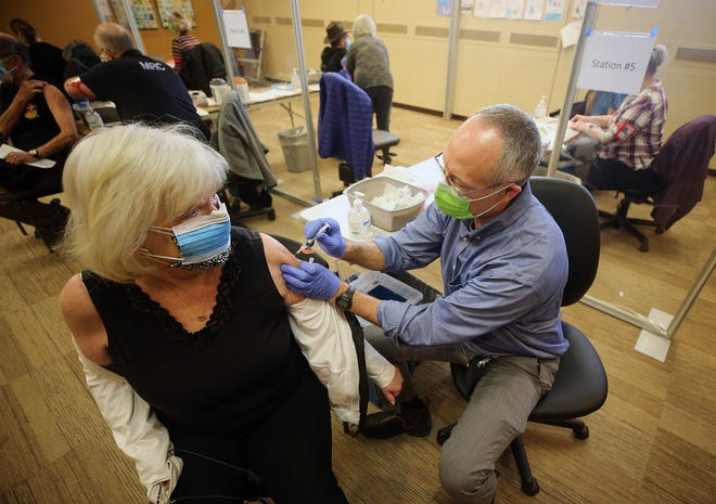 Kitsap Public Health District Health Officer Dr. Gib Morrow, gives Susan Carvey, of Silverdale, her shot during the Kitsap Public Health District and the Kitsap County Department of Emergency Management's first community COVID-19 vaccine clinic at the former St. Michael Medical Center in East Bremerton on Tuesday, Jan. 26, 2021.