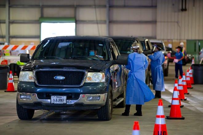Trabajadores de la salud aplican vacunas contra COVID-19 a automovilistas.