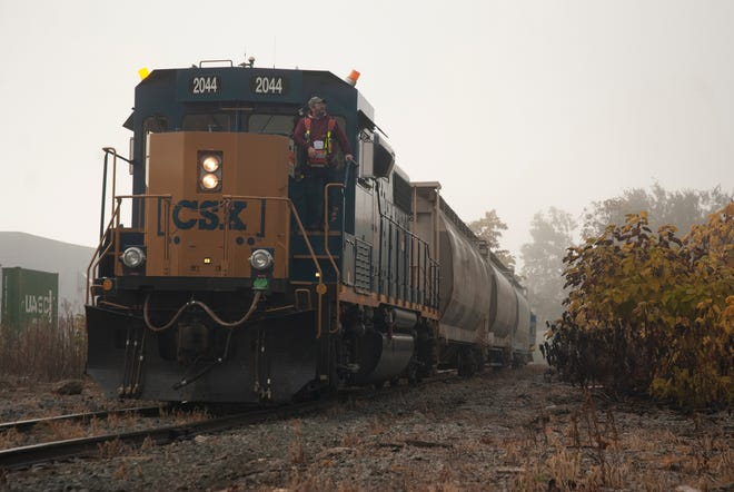 A CSX crew member wears a belt pack to operate the locomotive he is riding remotely in October 2019, on an industrial track just prior to a railroad crossing of Gest Street in Cincinnati. The orange light atop the locomotive is activated when a crew member operates the train remotely from the ground.
