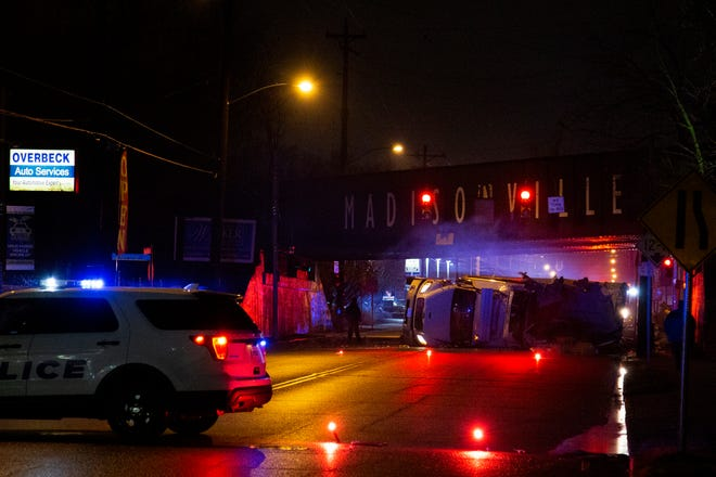 Police block off a section of Madison Road for a flipped truck, which struck the under side of the railroad bridge in the Madisonville neighborhood of Cincinnati on Monday, Jan. 25, 2021.