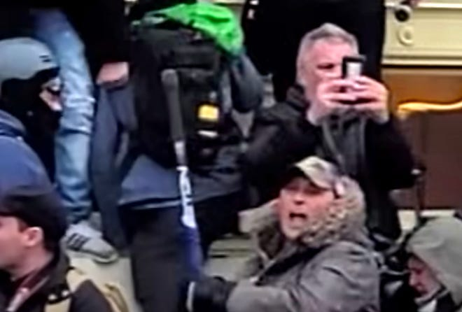 A YouTube videoand police body camera footage shown at a federal court hearing Monday caught the moment a manauthorities believeto beMichael Foyattacked police guarding an entrance to the Capitolwith a hockey stick that bore a Trump flag earlier in the day.