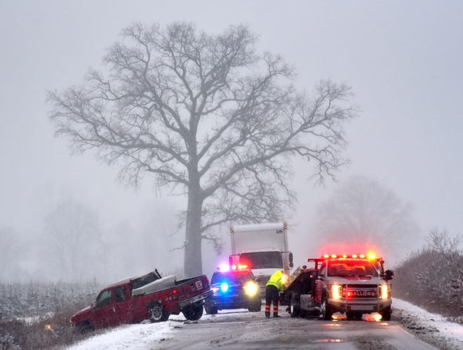 A Macomb County deputy briefly blocks Romeo Plank between 34 Mile and Armada Center in Armada Township as two tow trucks assist to pull a pickup truck out of the ditch, Tuesday morning, Jan. 26, 2021. The National Weather Service has issued a winter weather advisory for much of mid- and southeast Michigan until 4 p.m. The pickup drove away after being pulled out of the ditch.