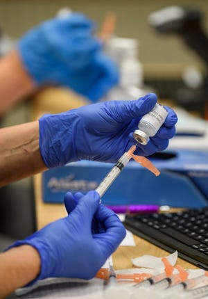 Registered nurses Michelle Alvey, front, and Anne Arrick, back, prepare shots of the Moderna COVID-19 vaccine before the start of a vaccine clinic at the Vanderburgh County Heath Department in Evansville, Ind., Tuesday afternoon, Jan. 26, 2021.
