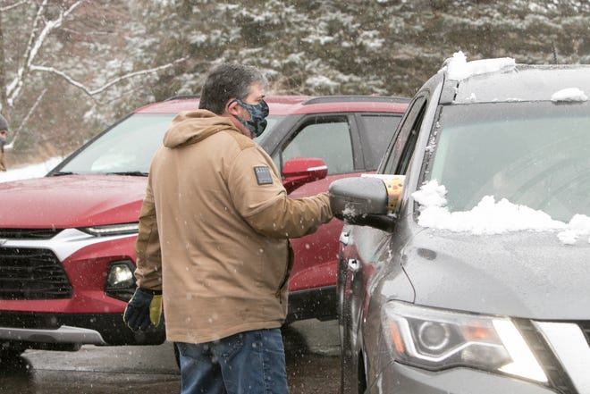Hamburg Township Clerk Mike Dolan hands out a box of masks at a drive-thru mask distribution event held outside of Hamburg Senior Community Center Tuesday, Jan. 26, 2021.