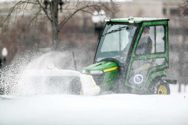 A a snow plow removes snow from the parking lot of the Michigan Historical Center on Tuesday, Jan. 26, 2021, in Lansing.